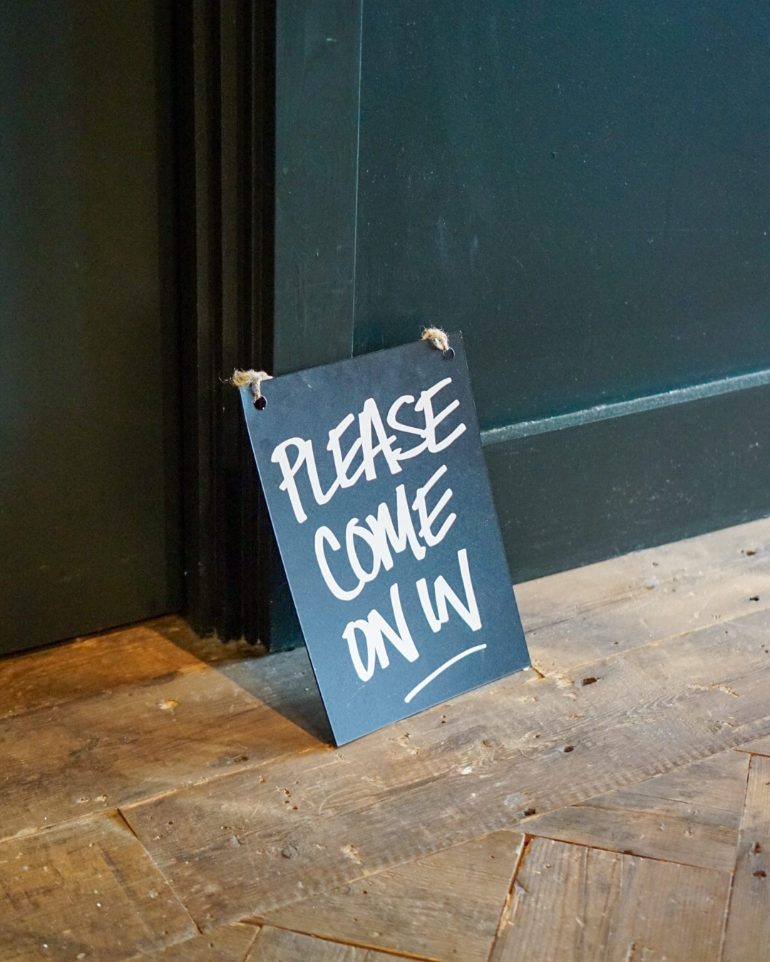 Lush Spa Renaissance treatment sign outside door. Black wooden board with white writing saying 'please come on in'