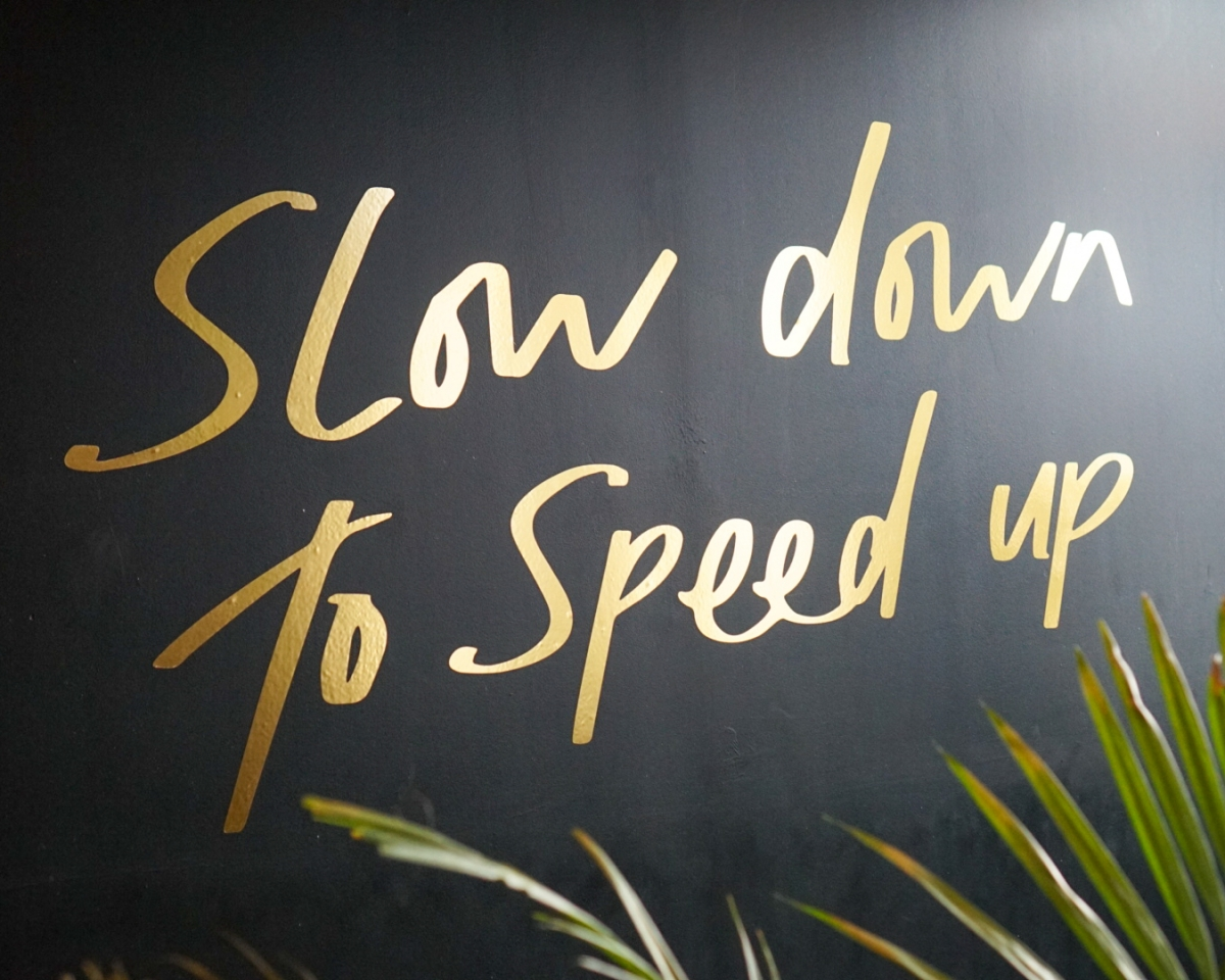 Slow down to speed up written in gold text on black wall at Lush Spa Birmingham