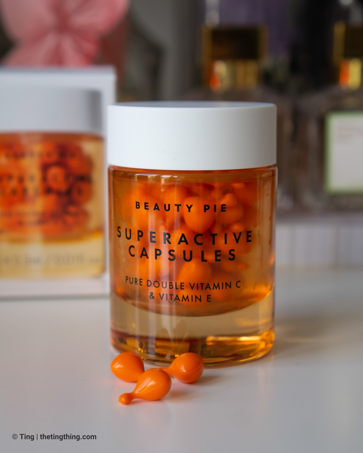 A jar of Beauty Pie Superactive Capsules on a white desk. This close up shot shows three capsules lying on the desk next to the jar.