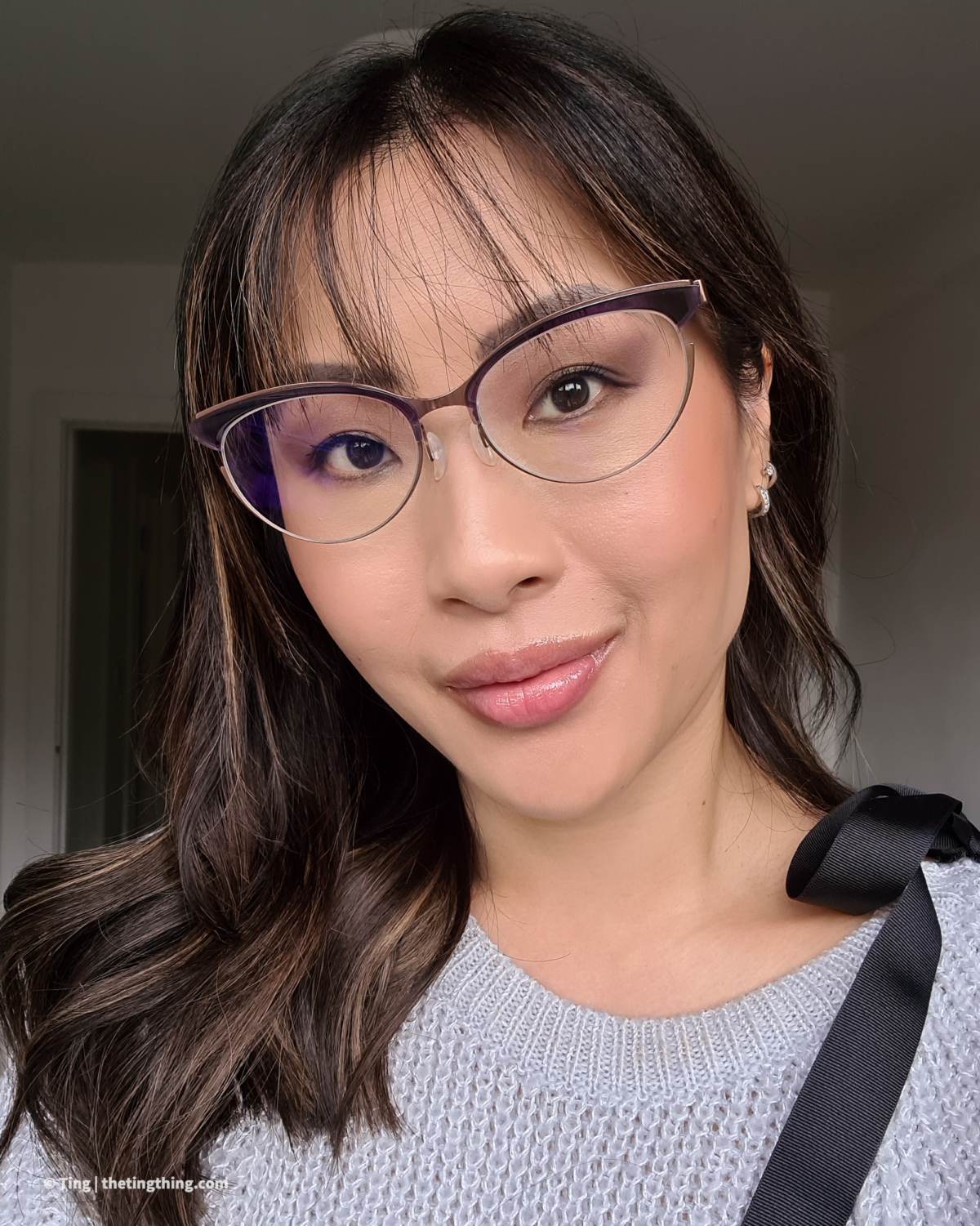 A Chinese woman with highlighted brunette hair smiles at the camera. Her hair is styled with waves and swept to one side. She has a wispy grown out fringe and large bronze and purple glasses. Shop small in Birmingham with a haircut and colour from award winning Aesthetics Hair.