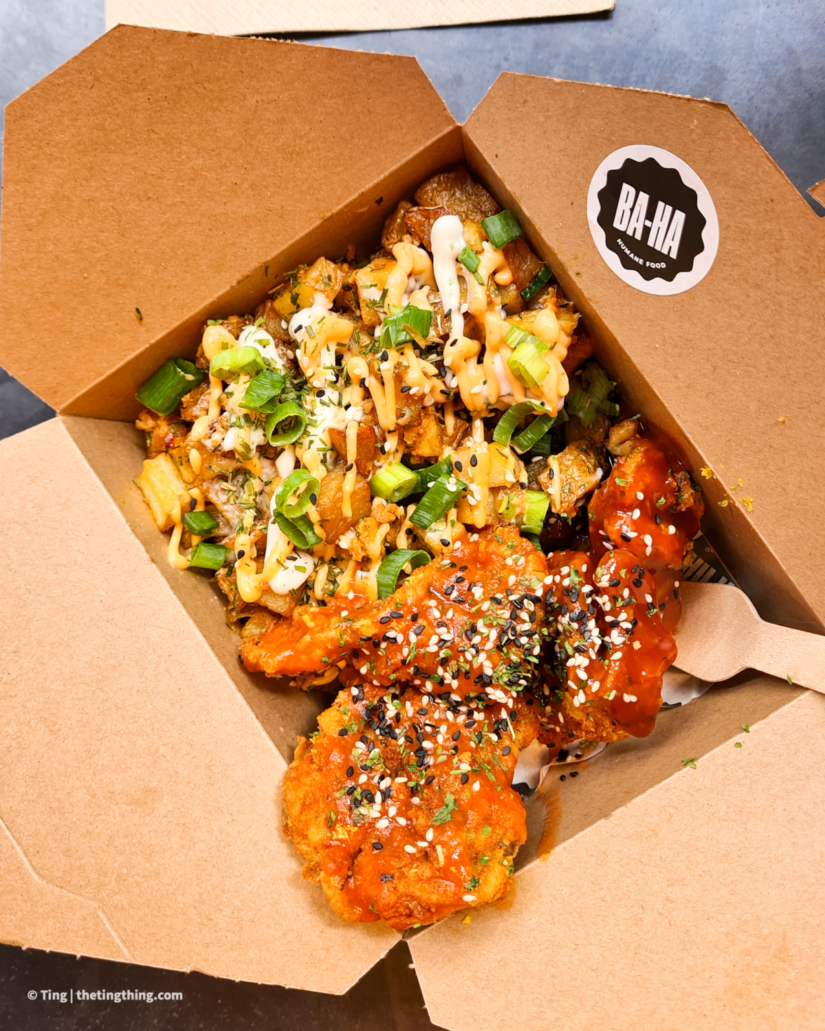 A cardboard lunchbox from Ba Ha Vegan at The Stag Digbeth. The box contains crispy potato cubes covered in sriracha mayo, spring onions and sesame seeds. Next to the potatoes are some 'chicken wings' made from deep fried crumbed king oyster mushrooms. The mushroom wings are covered in spicy sauce and a sprinkle of black and white sesame seeds.