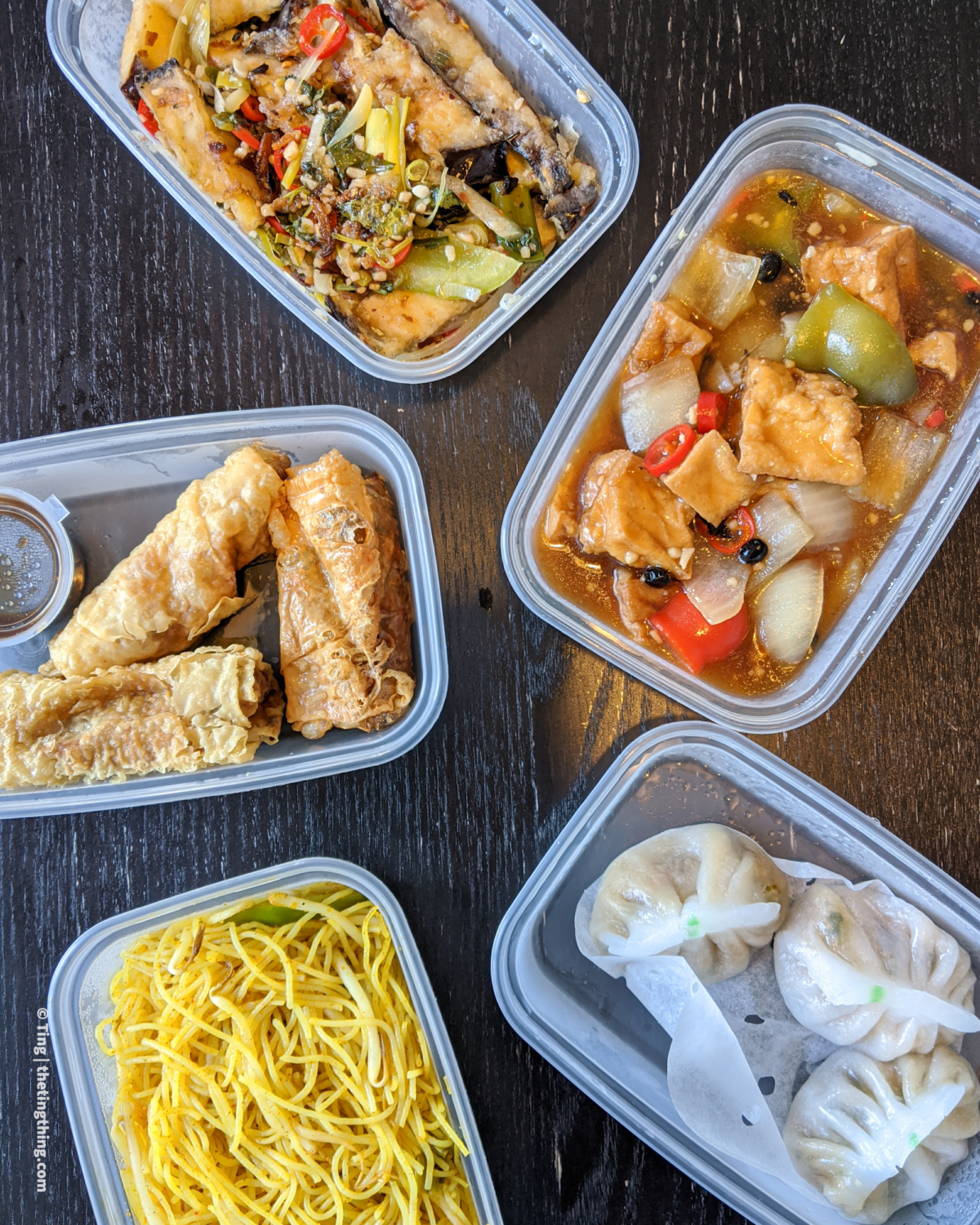 Five takeaway boxes containing a vegan Chinese takeaway delivery from Chung Ying. Each box has different foods. One has creamy white dumplings filled with veg. Another has yellow noodles. Another has deep fried crispy beancurd rolls with dipping sauce in a small pot. Another has tofu cubes and peppers in a black bean sauce. Another has aubergine and veg.