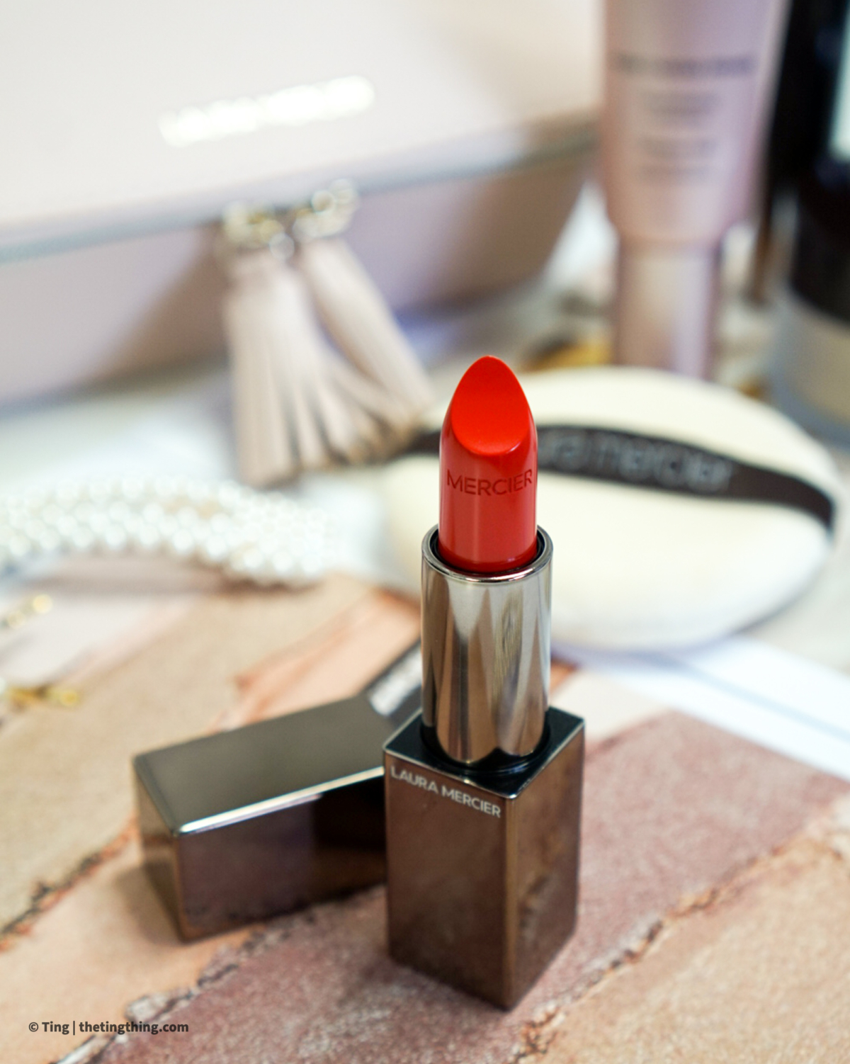 Close up shot of a red lipstick in gunmetal grey packaging.