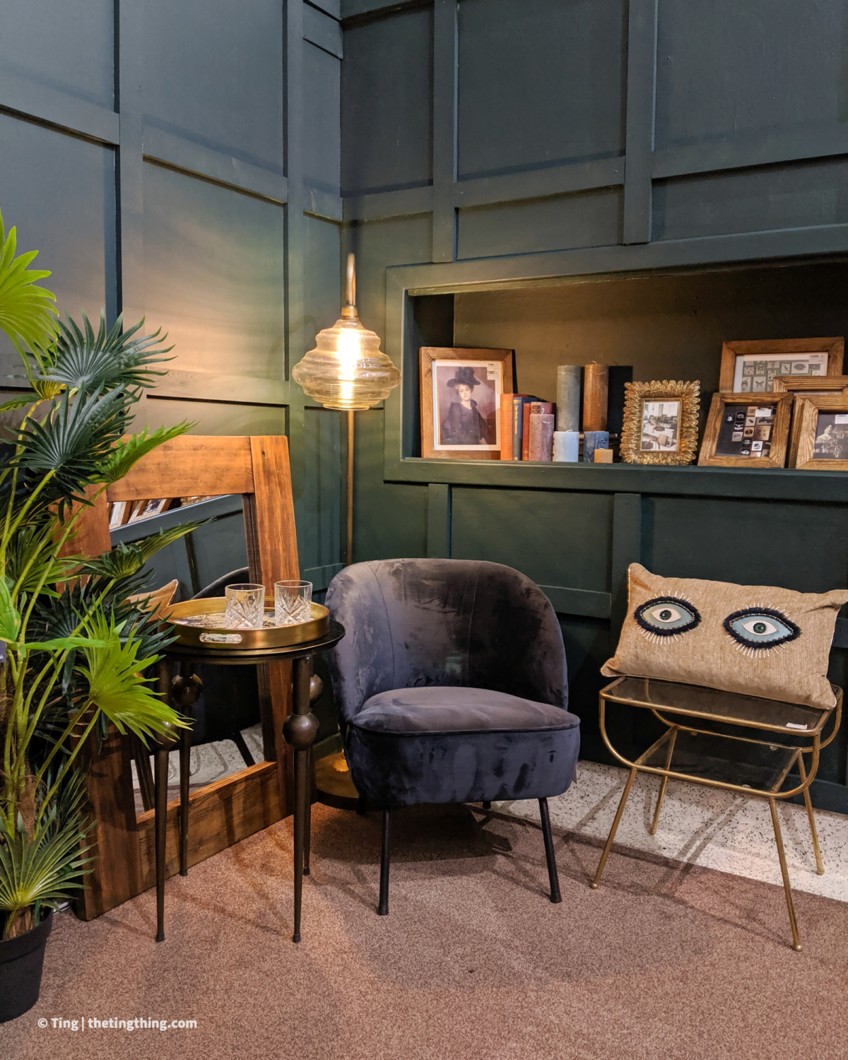 Shot of room corner with dark green panelled walls. A charcoal grey velvet armchair is surrounded by brass side tables, a tall floor lamp and a large wooden mirror leaning against the wall. A large plant is on the left of the chair, just in frame. Shop small in Birmingham at pretty homewares and lifestyle store Liv's in Solihull.