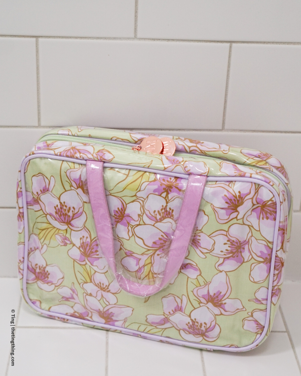 A Pixi Beauty toiletry bag in a pastel lilac and green floral design is sat on a white tiled bathroom counter.