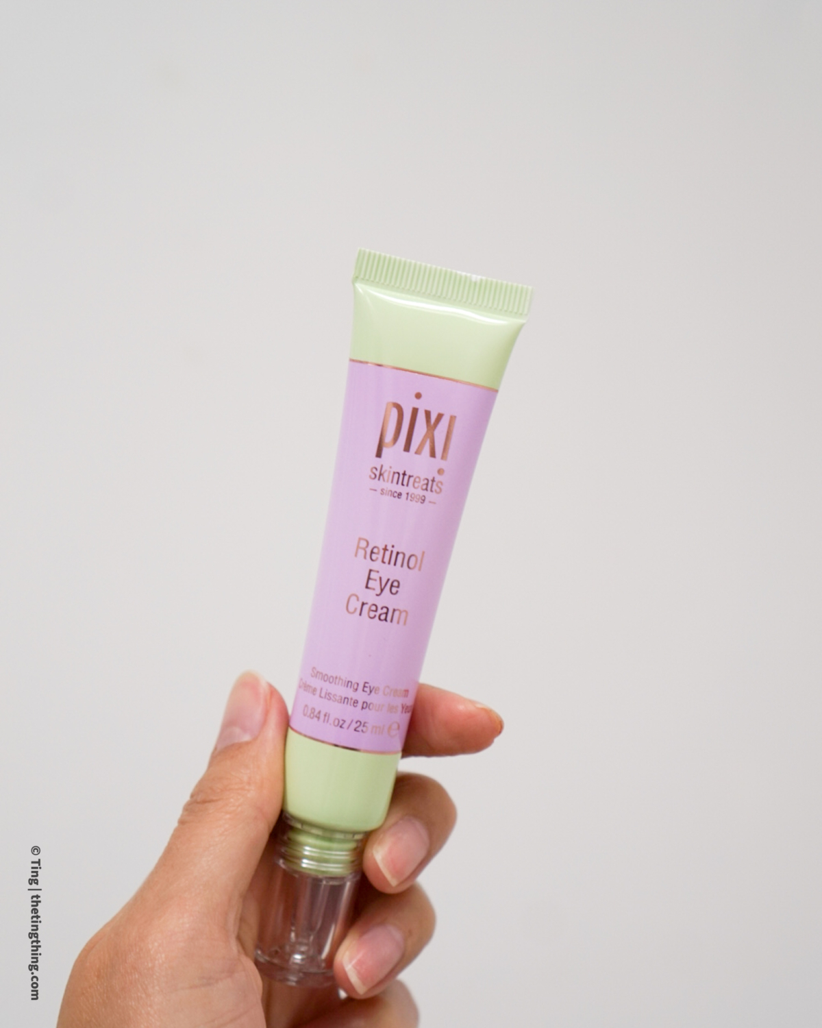 Tube of Pixi Beauty Retinol Eye Cream held by a Chinese woman against a pale wall background.