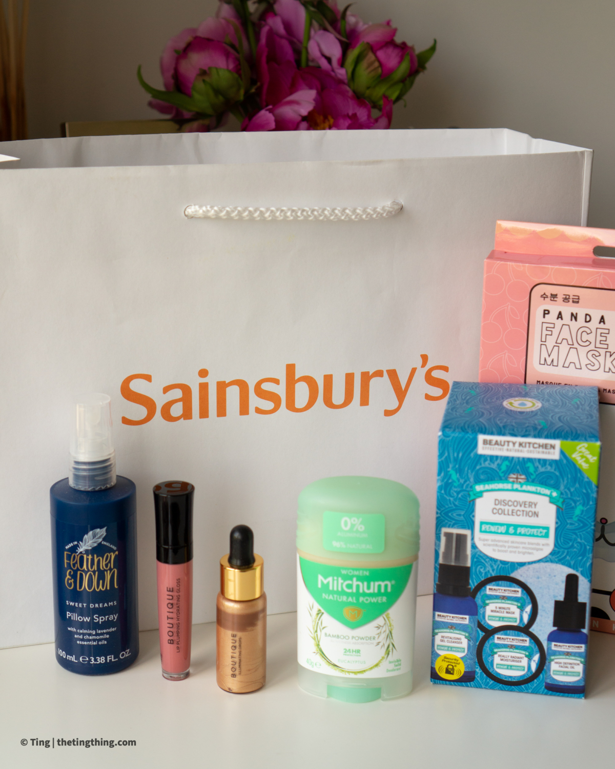 Sainsburys Beauty bag and beauty items lined up on a white desk