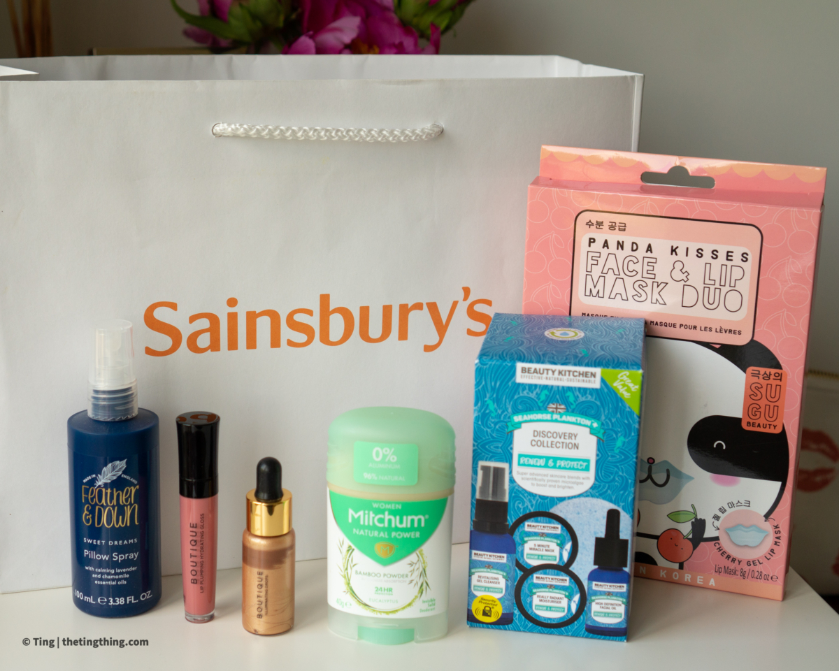 A selection of beauty products are lined up on a white desk in front of a white cardboard bag with the Sainsburys logo